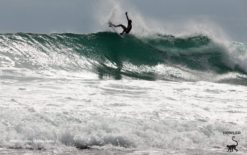 young tico surfer catching a wave